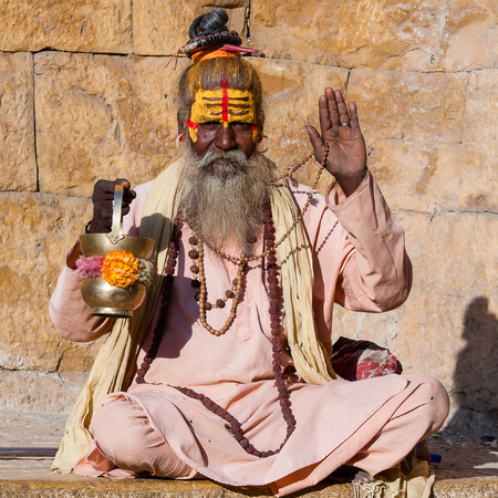 Hindu sadhu holy man, sits on the ghat, seeks alms on the street in Jaisalmer, Rajasthan, India