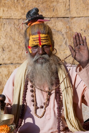 renunciation: Hindu sadhu holy man, sits on the ghat, seeks alms on the street in Jaisalmer, Rajasthan, India