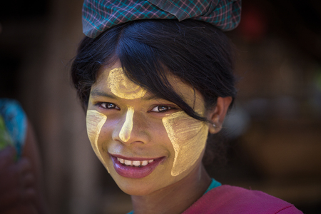 thanaka: MRAUK-U, MYANMAR - JANUARY 27, 2016: Unidentified young Myanmar girl with thanaka on her smile face is happiness. Thanaka is a yellowish-white cosmetic paste made from ground bark. Editorial
