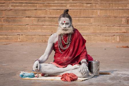 sadhu: VARANASI, INDIA - DECEMBER 1, 2012 : Unidentified Hindu sadhu holy man, sits on the ghat near the Ganges river in Varanasi, India. Tourism has drawn many alleged fake sadhus to Varanasi Editorial