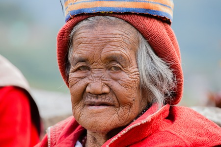 filipino people: BANAUE, PHILIPPINES - JANUARY 24, 2014 : Portrait old Filipino woman of Ifugao mountain tribes in national dress next to rice terraces. Ifugao - the  mountain people in the Philippines.