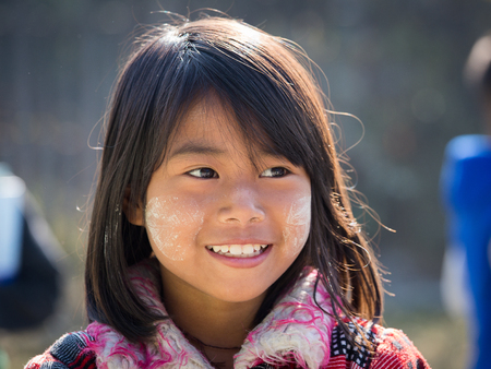 thanaka: INLE LAKE, MYANMAR - JANUARY 13, 2016: Unidentified young Myanmar girl with thanaka on her smile face is happiness. Thanaka is a yellowish-white cosmetic paste made from ground bark. Editorial