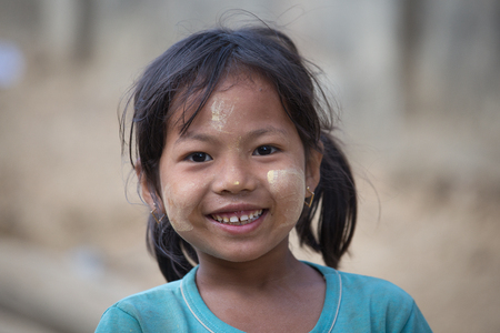 thanaka: MRAUK-U, MYANMAR - JANUARY 26, 2016: Unidentified young Myanmar girl with thanaka on her smile face is happiness. Thanaka is a yellowish-white cosmetic paste made from ground bark.