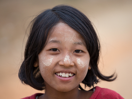 thanaka: MRAUK-U, MYANMAR - JANUARY 28, 2016 : Unidentified young Myanmar girl with thanaka on her smile face is happiness. Thanaka is a yellowish-white cosmetic paste made from ground bark. Editorial