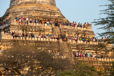 climbed: BAGAN, MYANMAR - JANUARY 20, 2016: Unidentified tourists climbed to the pagoda, to take pictures of the sunset over Bagan