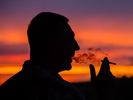 only one mid adult male: Silhouette of a man who smokes a cigarette on a sunset background, close up Stock Photo