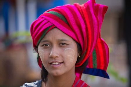 thanaka: INLE LAKE, MYANMAR - JANUARY 12, 2016: Unidentified young Myanmar girl with thanaka on her smile face is happiness. Thanaka is a yellowish-white cosmetic paste made from ground bark.