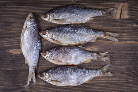 fish rearing: Dry fish on a wooden background, close up