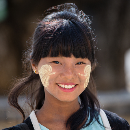 thanaka: MANDALAY, MYANMAR - JANUARY 16, 2016: Unidentified young Myanmar girl with thanaka on her smile face is happiness. Thanaka is a yellowish-white cosmetic paste made from ground bark.