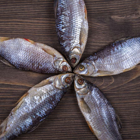 rearing of fish: Dry fish on a wooden background, close up