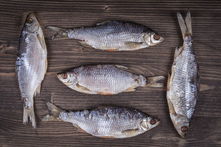 fished: Dry fish on a wooden background, close up
