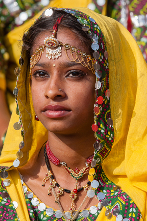 ethnic attire: PUSHKAR, INDIA - NOVEMBER 21, 2012 : Portrait of Indian girl in colorful ethnic attire at Pushkar Camel Mela in Rajasthan, India. Pilgrims and camel traders flock to the holy town for the annual fair