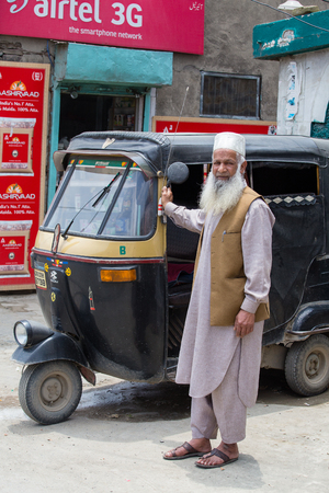 auto rickshaw: SRINAGAR, INDIA - JULE 11, 2015: Auto rickshaw taxis and muslim man on a road in Kashmir, India. These iconic taxis have recently been fitted with CNG powered engines in an effort to reduce pollution Editorial