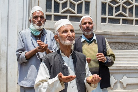 poverty india: SRINAGAR, INDIA - JUNE 11, 2015: Unidentified Indian muslim men begging on the streets near the mosque in Srinagar, Kashmir. India. Poverty is a major issue in India