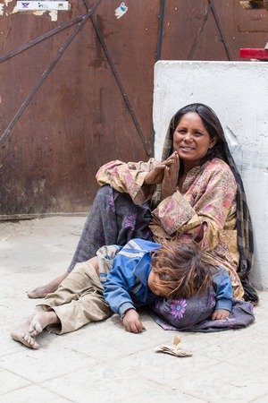 poverty india: LEH, INDIA - JUNE 24, 2015: Unknown beggar woman with a child begging near Buddhist temple in Leh, Ladakh. Poverty is a major issue in India