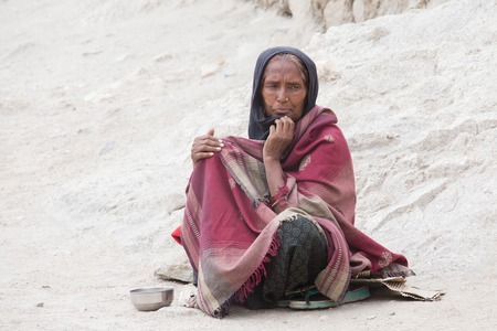 begs: LEH, INDIA - JUNE 24, 2015: Unknown poor woman begs for money from a passerby on the street in Leh, Ladakh. Poverty is a major issue in India