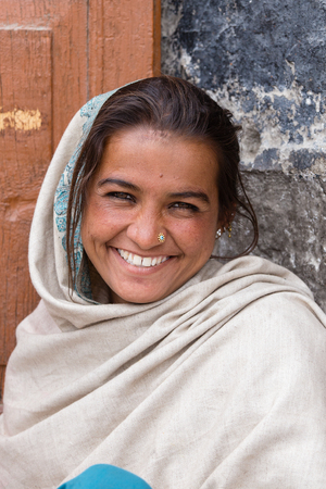 begs: LEH, INDIA - JUNE 24, 2015: Unknown smiling poor girl begs for money from a passerby on the street in Leh, Ladakh. Poverty is a major issue in India