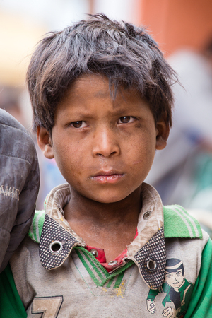 impoverished: LEH, INDIA - JUNE 21, 2015: Unidentified beggar young boy on the street in Leh, Ladakh. Poverty is a major issue in India
