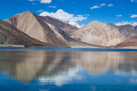 Sunny day at Pangong Lake and Himalayan mountain. Pangong Lake, is an endorheic lake in the Himalayas situated at a height of about 4,350 m in Ladakh, India. It is 134 km long from India to Tibet Stock Photo
