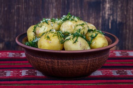 Boiled potatoes with dill and garlic in butter on a plate close up. Stock Photo