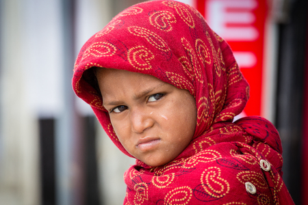 SRINAGAR, INDIA - JUNE 10, 2015: Unidentified beggar girl begs for money from a passerby in Srinagar, Kashmir. Poverty is a major issue in India