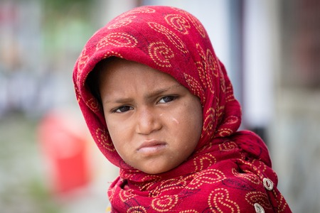 passerby: SRINAGAR, INDIA - JUNE 10, 2015: Unidentified beggar girl begs for money from a passerby in Srinagar, Kashmir. Poverty is a major issue in India
