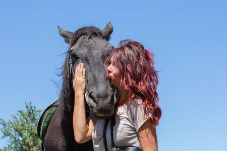 Portrait of young beautiful woman with black horse in nature. Kiev, Ukraine