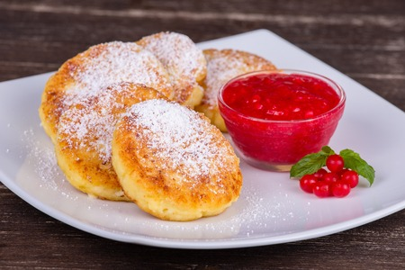 Cheese pancakes with berry jam in white plate. Close up