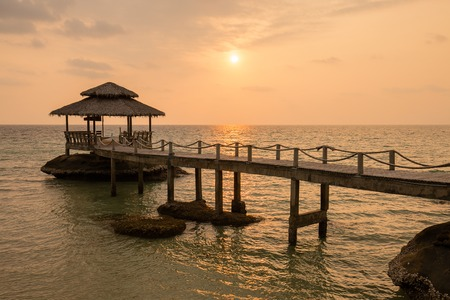 Tropical sand beach with pier near sea water on the sunset