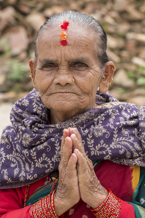 KATHMANDU, NEPAL - SEPTEMBER 29, 2016 : Portrait old woman in traditional dress with folded hands in street Kathmandu, Nepal. Close up Editorial