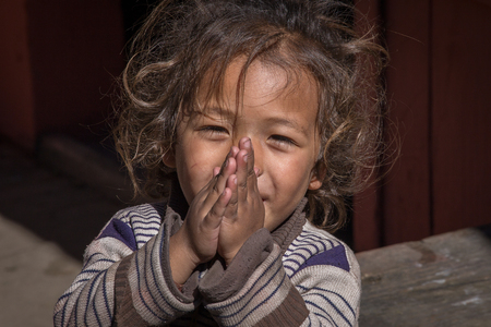 MANANG VILLAGE, WESTERN NEPAL - OCTOBER 14, 2016 : Portrait young girl with folded hands in street . Close up Editorial