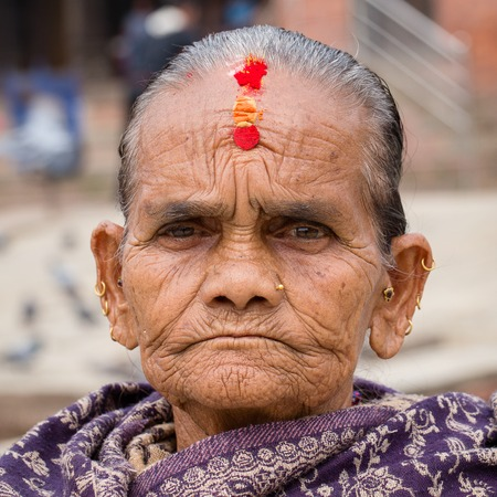 pauper: KATHMANDU, NEPAL - SEPTEMBER 29, 2016 : Portrait old women in traditional dress in street Kathmandu, Nepal