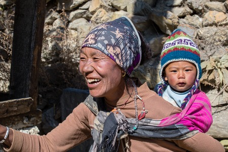 HIMALAYAS, ANNAPURNA REGION, NEPAL - OCTOBER 17, 2016 : Portrait nepalese mother and child on the street in Himalayan village, Nepal