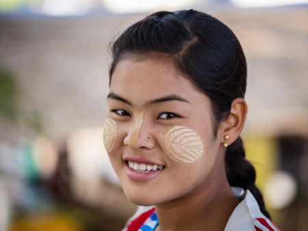 thanaka: MANDALAY, MYANMAR - JANUARY 17, 2016: Unidentified young Myanmar girl with thanaka on her smile face is happiness. Thanaka is a yellowish-white cosmetic paste made from ground bark.