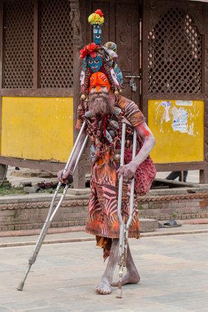 KATHMANDU, NEPAL - SEPTEMBER 29, 2016 : Sadhu, holy man patient on crutches in Pashupatinath Temple, Kathmandu Nepal