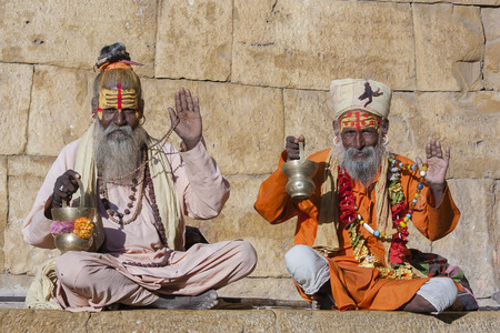Two hindu sadhu holy man, sits on the ghat, seeks alms on the street in Jaisalmer, Rajasthan, India. Close up photo