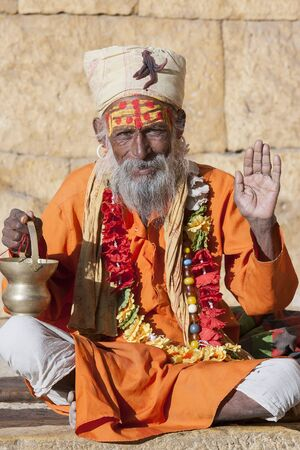 Hindu sadhu holy man, sits on the ghat, seeks alms on the street in Jaisalmer, Rajasthan, India. Close up photo