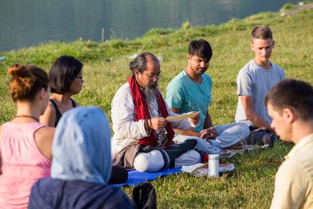 POKHARA, NEPAL - OCTOBER 07, 2016 : Tibetan Lama conducts classes with sunsurfers people on meditation and yoga near the lake