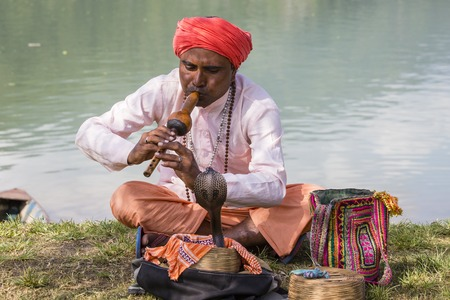 charmer: POKHARA, NEPAL - OCTOBER 07, 2016 : Portrait of snake charmer adult man in turban and cobra sitting near the lake Editorial