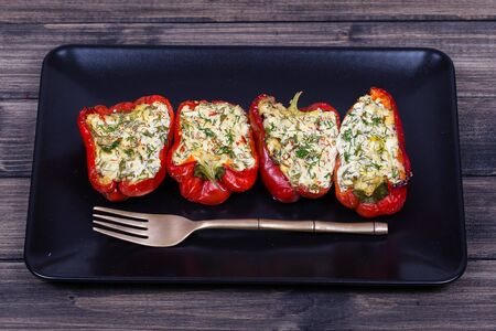 red peppers: Red peppers stuffed with cream cheese with herbs and garlic, baked in grill in black plate, close up