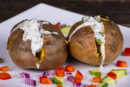 Baked potato with vegetables and sour cream. Close up Stock Photo