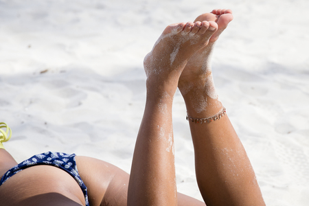 Womans beautiful legs on the beach, close up Stock Photo
