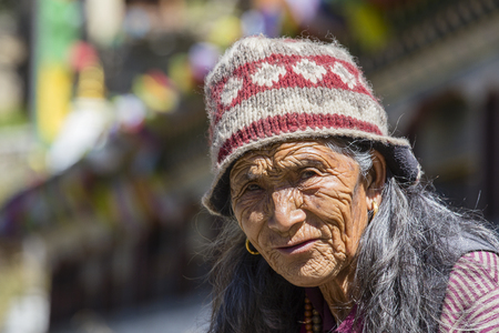 HIMALAYAS, ANNAPURNA REGION, NEPAL - OCTOBER 15, 2016 : Unidentified old Nepalese woman with wrinkled face portrayed in a Himalayan village in Nepal Editorial