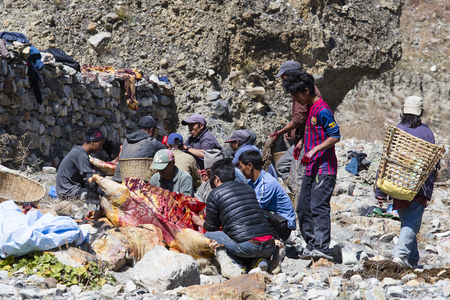 carcasses: HIMALAYAS, ANNAPURNA REGION, NEPAL - OCTOBER 17, 2016 : Tibetan butcher men butchering yak carcasses for sale in the local market Editorial