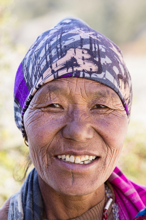 HIMALAYAS, ANNAPURNA REGION, NEPAL - OCTOBER 17, 2016 : Unidentified old Nepalese woman with wrinkled face portrayed in a Himalayan village in Nepal