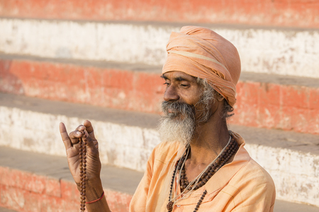 VARANASI, INDIA - JANUARY 25, 2017 : Portrait of Shaiva sadhu, holy man on the ghats of the Ganges river in Varanasi, India . Close up
