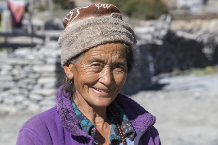 HIMALAYAS, ANNAPURNA REGION, NEPAL - OCTOBER 16, 2016 : Unidentified old Nepalese woman with wrinkled face portrayed in a Himalayan village in Nepal Editorial