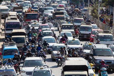 KATHMANDU, NEPAL - 25 DE OCTUBRE DE 2016: El tráfico se mueve lentamente a lo largo de una carretera transitada en Kathmandu, Nepal. Atestado atasco carretera en la ciudad Foto de archivo - 75773857