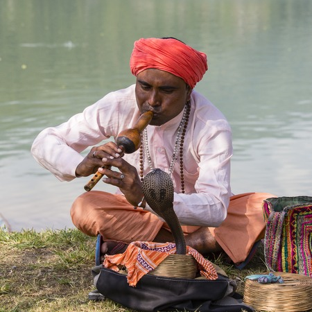 street musician: POKHARA, NEPAL - OCTOBER 07, 2016 : Portrait of snake charmer adult man in turban and cobra sitting near the lake Editorial
