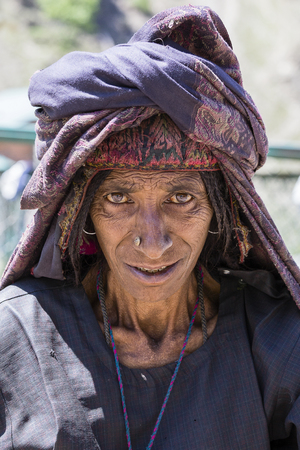 SRINAGAR, INDIA - JUNE 12, 2015: Unidentified beggar woman begs for money from a passerby in Srinagar, Kashmir. Poverty is a major issue in India Editorial